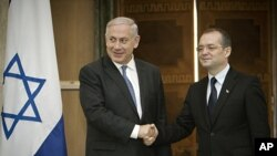 Israeli Prime Minister Benjamin Netanyahu, left, shakes hands with his Romanian counterpart Emil Boc, right, at Victoria Palace in Bucharest, Romania, July 6, 2011