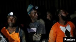 Miners look on after they retrieved the bodies of two other miners from Johannesburg's oldest gold mine in Langlaagte, South Africa, Sept. 13, 2016.