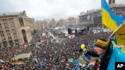 2013年12月8日在乌克兰首都基辅的独立广场,亲欧盟的群众举行抗议活动,一名少年挥舞着国旗,支持示威活动。