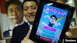 Takuya Hirai, Director of Internet Media Division of Japan's ruling Liberal Democratic Party, poses with an iPad displaying 'Abe Pyon,' LDP's official game application program featuring Shinzo Abe, Japan's prime minister and LDP's leader, at the LDP headq