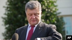 Ukrainian President Petro Poroshenko checks his watch while speaking to members of the media outside the West Wing of the White House, following his meeting with President Barack Obama, Sept. 18, 2014.