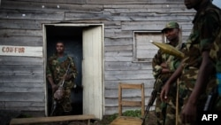 Para pejuang pemberontak M23 berdiri di luar rumah kayu di desa Kanyarucinya, 6 kilometer dari Goma, di wilayah timur Republik Demokratik Kongo (DRC) (18/11).