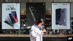FILE - A woman walks by posters advertising smartphones in Seoul, South Korea, Oct. 17, 2017. Researchers have completed the first survey of valuable materials they say are waiting to be mined from Europe's vast landfills and scrapyards. Smartphones have concentrations of gold that are more than 25 times as high as the richest underground ores and are far easier to extract.