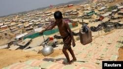 一名羅興亞男孩在孟加拉國的一個羅興亞人難民營裡挑水。 (2018年3月22日)