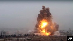 This frame grab from video provided by Thiqa news agency, a Syrian opposition media outlet that is consistent with independent AP reporting, shows flames rises from an explosive vehicle bomb that attacked a Syrian government position, in southwest of Alep