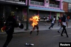 Un hombre corre envuelto en llamas durante una protesta el domingo en Caracas.