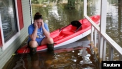 A woman sits on a kayak that is floating on her friend's porch as the house is cleaned of possessions after Tropical Storm Harvey in Orange, Texas, Sept. 1, 2017.