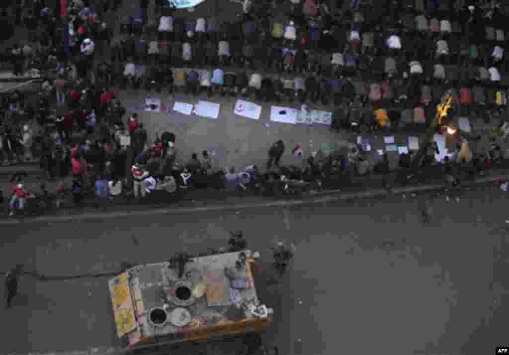 Anti-government protesters pray near Egyptian solders in Tahrir, or Liberation Square in Cairo, Egypt, Tuesday, Feb. 1, 2011. More than a quarter-million people flooded into the heart of Cairo Tuesday, filling the city's main square in by far the largest