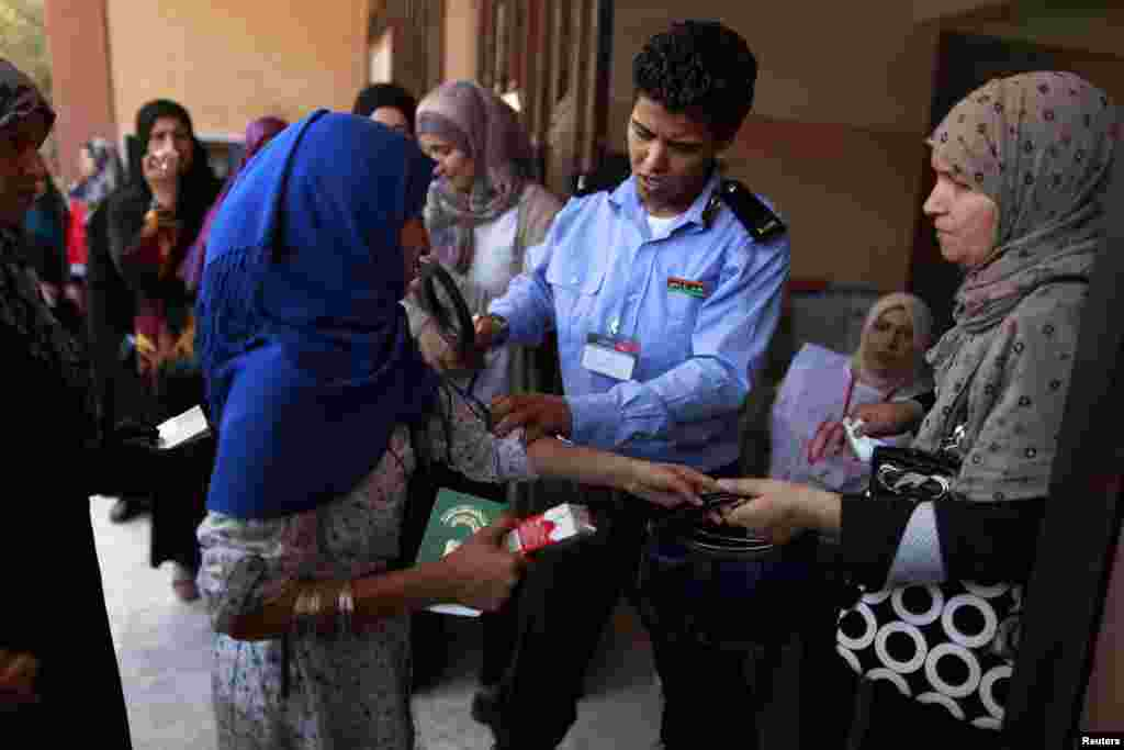 A policewoman searches a voter during the National assembly election at a polling station in Tripoli July 7, 2012. Libyans began voting in their first free national election in 60 years on Saturday, a poll designed to shake off the legacy of Muammar Gadda