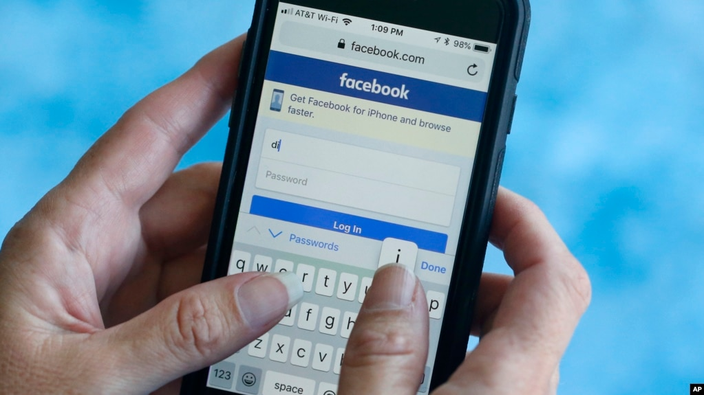 FILE - A Facebook start page is shown on a smartphone in Surfside, Florida. Aug. 21, 2018. The social media giant Facebook said late Wednesday Aug. 22, 2018, it has banned a quiz app for refusing to be audited and concerns that data on as many as 4 million users was misused, after it found user information was shared with researchers and companies.