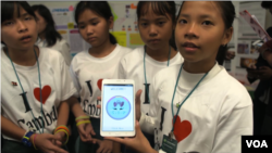 Lorn Dara Soucheng, 12, (middle), team leader and other team members show the Cambodia Identity Product app that they have created at the Technovation Challenge World Pitch Summit girl mobile app competition at Google headquarters in Mountain View, CA, Wednesday, August 09, 2017. (Sophat Soeung/VOA Khmer)