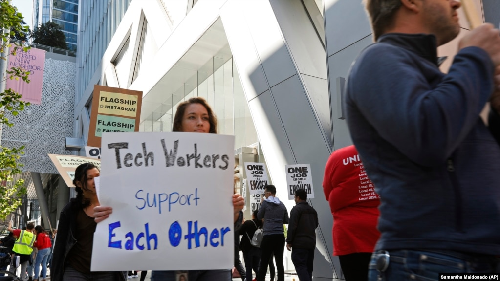 In this photo taken July 16, 2019, tech workers march to support Facebook's cafeteria workers, who were rallying for a new contract with their company Flaghship in San Francisco. (AP Photo/Samantha Maldonado)