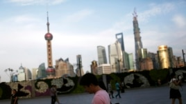 A man looks at his iPad in front of the financial distric in Shanghai on Sept. 24, 2013.