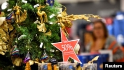 "FILE PHOTO: A star-shaped placard hanging from a Christmas tree states ""Take 50% Off Ticketed Price"" at a Macy's store as pre-Thanksgiving and Christmas holiday shopping accelerates at the King of Prussia Mall in King of Prussia, Pennsylvania, U.S."