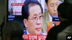 지난 2013년 12월 한국 서울역에서 시민들이 북한 장성택 실각 소식을 알리는 뉴스를 보고있다. (자료사진)