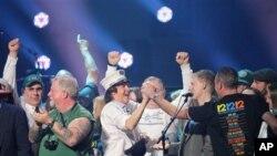 Paul McCartney trên sân khấu cùng các nhân viên cứu hỏa tại Madison Square Garden, New York.