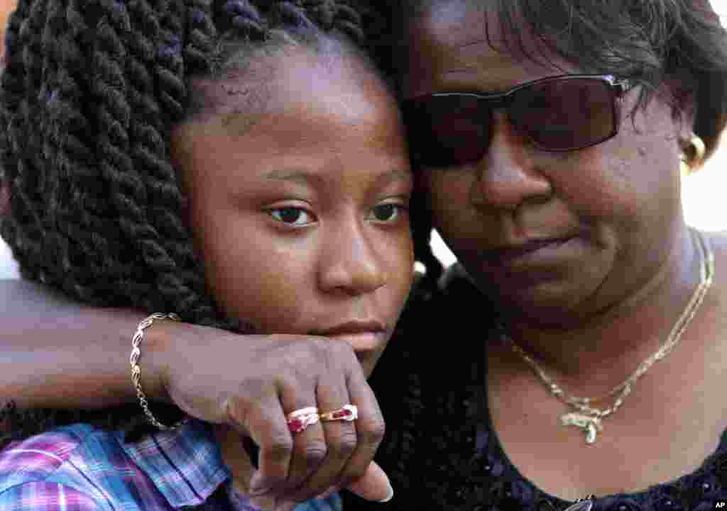 Antonee Martin, left, and her mother Latrechia Jackson, right, visit the memorial site set up in front of the Emanuel AME Church, June 18, 2015 in Charleston, S.C.