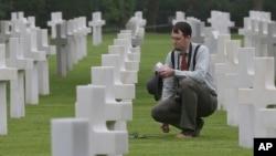 Matthew Conway, de Burlington, Connecticut, coloca una flor en la tumba de su tío John J. Ketter, en el cementerio militar estadounidense Colleville, en Colleville sur Mer, en el oeste de Francia, el miércoles, 6 de junio de 2018.