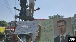 Những người biểu tình phản đối Tổng thống Syria, sau buổi lễ cầu nguyện ngày thứ Sáu, cầm các biểu ngữ với dòng chữ 'Tên độc ác, điếc, đui mù', hoặc 'Hãy từ chức đi con người độc ác'