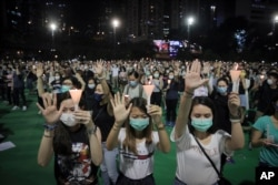 """Participants gesture with five fingers, signifying the """"Five demands - not one less"""" during a vigil for the victims of the 1989 Tiananmen Square Massacre at Victoria Park in Causeway Bay, Hong Kong, June 4, 2020."""