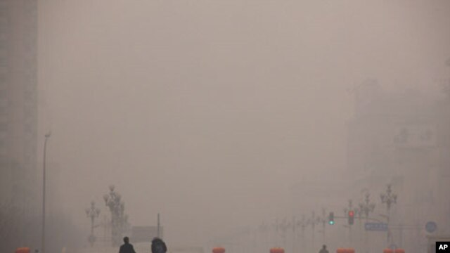 Pedestrians walk along a square as a security guard stands nearby on a hazy day in Beijing January 18, 2012.