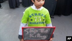 """In this citizen journalism image made on a mobile phone, a Syrian boy carries a board that reads:"""" stop the killing,"""" during a protest in Daraya, southwest of Damascus, Syria, April 25, 2011"""