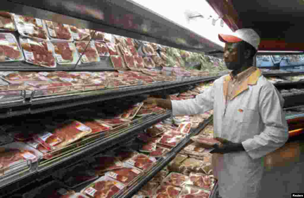 A shop worker arranges packaged meat at a leading supermarket in Harare January 16, 2012. Zimbabwe's headline consumer inflation rate quickened to 4.9 percent year-on-year in December, higher than government's year-end target for 2011.