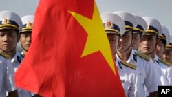 FILE - Vietnam People's Navy personnel carry their country's national flag.