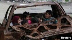 Niños juegan en un carro destrozado en la ciudad de n Aleppo, Syria, Feb. 16, 2015.