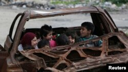 Children play inside the wreckage of a burnt vehicle at al-Myassar neighborhood in Aleppo, Syria, Feb. 16, 2015.