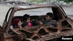Children play inside the wreckage of a burnt vehicle at al-Myassar neighborhood in Aleppo, Syria, Feb. 16, 2015.