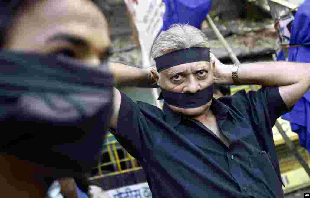 An Indian ties a black band as he arrives to attend a gathering to mourn the death of a 23-year-old gang rape victim, in Mumbai, Saturday, Dec. 29, 2012.