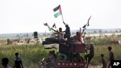 មនុស្សកំពុងគ្រវីទង់ជាតិក្នុងពេលបើកបរម៉ូតូដឹកកង់ឡានដើម្បីយកទៅដុតធ្វើបាតុកម្មនៅតំបន់ Gaza ជាប់ព្រំដែនអ៊ីស្រាអែល កាលពីដើមខែសីហា ២០១៨។
