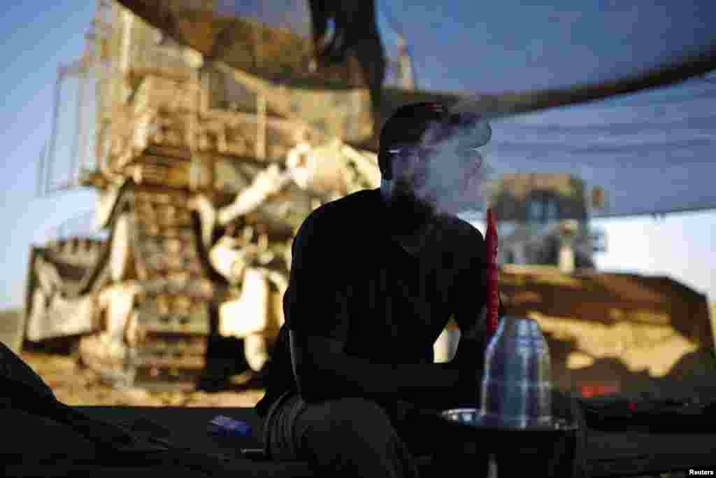 An Israeli soldier smokes a hookah at a staging area near the border with the Gaza Strip, Aug. 7, 2014.