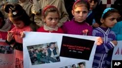 ARSIP – Anak-anak Pakistan mengangkat poster dengan foto-foto korban serangan ke sekolah di Peshawar dalam peringatan setahun serangan tersebut, Selasa, 15 Desember 2015 (foto: AP Photo/Anjum Naveed)