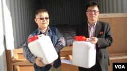 미국의 대북 지원단체인 '원 그린 코리아 무브먼트'의 김호진 대표와 북측 인사가 25일 남포항에 도착한 씨앗이 담긴 통을 들고 있다