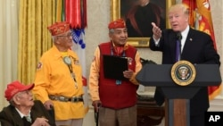 FILE - President Donald Trump speaks during a meeting with Navajo Code Talkers Fleming Begaye, seated at left, Thomas Begay, second from left, and Peter MacDonald in the Oval Office of the White House, Nov. 27, 2017. Begaye died May 10, 2019, in Arizona at 97.