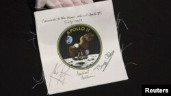 An Apollo 11 emblem, flown into lunar orbit and signed by the crew - Neil Armstrong, Michael Collins, and Buzz Aldrin, which is estimated at $40,000 to $60,000, is displayed as part of the upcoming Space History Sale at Bonham's auction house in New York, April 4, 2014.