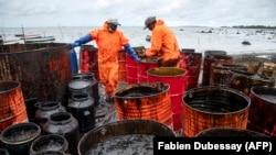 Des ouvriers ramassent des fuites de pétrole sur la plage de la Rivière des Créoles le 15 août 2020, en raison de la fuite de pétrole du navire MV Wakashio. (Photo by Fabien Dubessay / AFP)