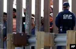 2018年11月25日在美国加州圣迭戈的边界栅栏两侧,有美国海关和边境保护局人员和企图进入美国的移民。
