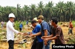 Presiden Jokowi menyalami petani sawit di tengah kunjungannya ke Rokan Hulu, Riau. (Foto: Humas Setneg)