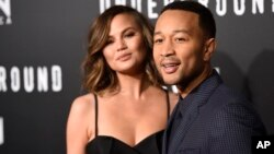"FILE - John Legend, executive producer of ""Underground,"" poses with his wife Chrissy Teigen at the season two premiere of the television series."
