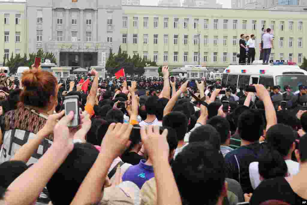 Residents take pictures with their cell phones as government officials address demonstrators in Dalian. (Reuters)
