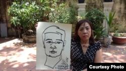 Luật sư Nguyễn Thị Dương Hà cầm bức tranh tự hoạ của TS luật Cù Huy Hà Vũ 1 ngày trước khi ông tuyệt thực.