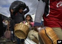 La niña Brittany Ríos, de Honduras y parte de la caravana de migrantes que busca asilo en Estados Unidos, lleva animales de peluche en una canasta de mimbre, el viernes 30 de noviembre de 2018, en Tijuana, México.