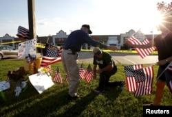 Warga meletakkan bendera Amerika untuk mengenang korban di depan Pusat Karir Angkatan Bersenjata di Chattanooga, Tennessee, July 16, 2015.