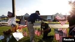 Warga yang berduka menempatkan bendera di lokasi penenbakan di depan Pusat Penerimaan Calon Tentara AS di Chattanooga, Tennessee (16/7).