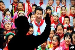 在北京展览馆前面,人们前往参观《砥砺奋进的五年》大型成就展里有中国主席习近平带着少先队的红领巾和少年儿童的合影(2017年10月23日)