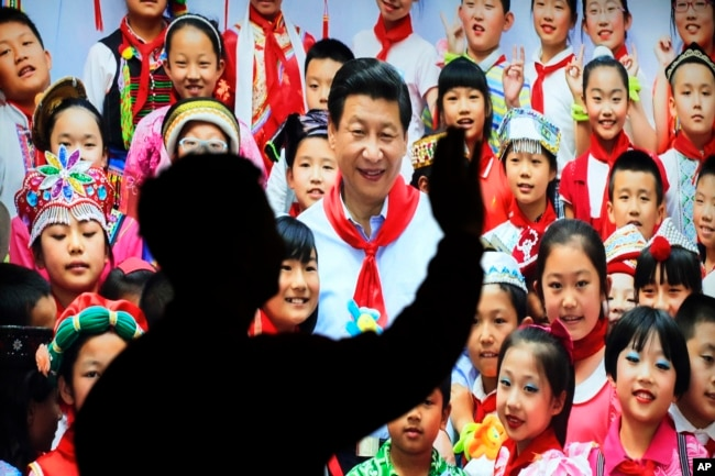 在北京展覽館前面,人們前往參觀《砥礪奮進的五年》大型成就展裡有中國主席習近平帶著少先隊的紅領巾和少年兒童的合影(2017年10月23日)