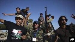 利比亚过渡政府的战士9月21日在俘获敌方一辆装甲车后欢欣雀跃